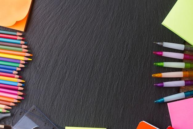 Voltar ao material escolar - lápis e canetas como moldura no quadro-negro