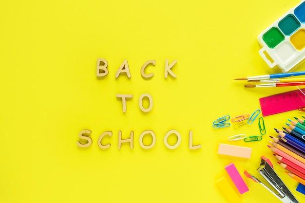 Voltar para a escola bsckground. postura plana de material escolar em fundo amarelo.