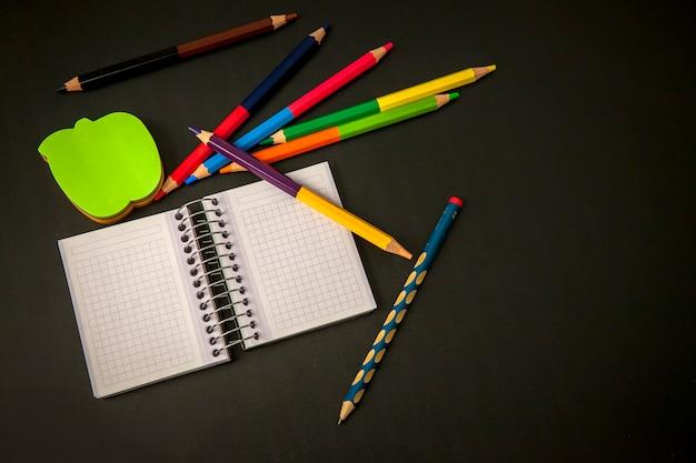 Voltar para a escola: caderno com lápis e lápis de cor em um quadro negro