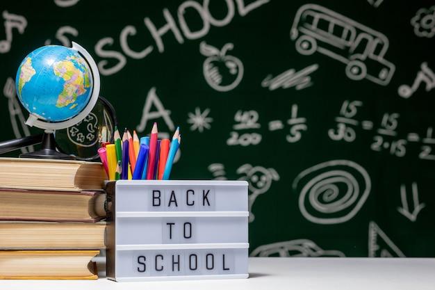 Voltar para a escola com livros, lápis e globo na mesa branca em um quadro negro verde