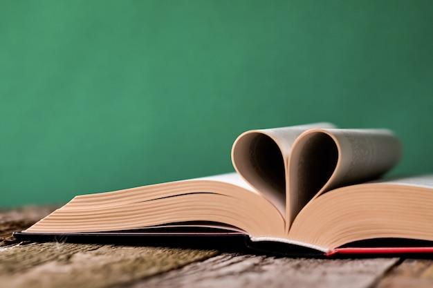Voltar para a escola com o livro aberto na superfície de madeira velha