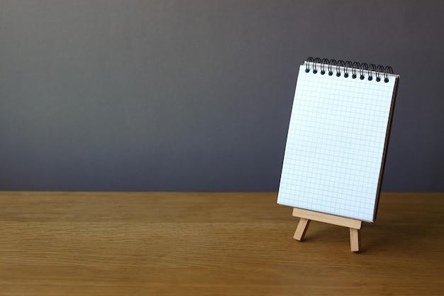 Voltar para a escola com o notebook aberto em cavalete em miniatura na superfície de madeira em um pano de fundo cinza