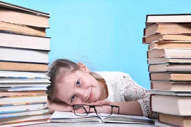 Voltar para a escola. criança bonita e industriosa feliz está sentado em uma mesa dentro de casa. criança está aprendendo na sala de aula em casa. montanhas de livros nas laterais