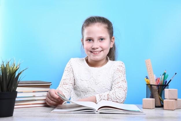 Voltar para a escola. criança bonita e industriosa feliz está sentado em uma mesa dentro de casa. garoto está aprendendo em sala de aula. quarentena. criança está aprendendo em casa.