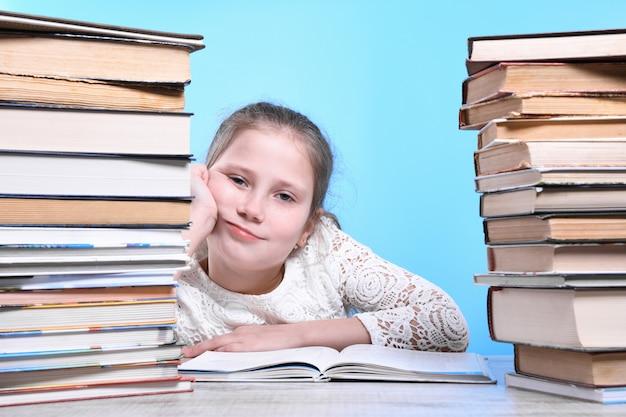 Voltar para a escola. criança bonita e industriosa feliz está sentado em uma mesa dentro de casa. garoto está aprendendo na aula. montanhas de livros nas laterais