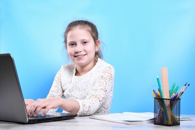 Voltar para a escola. criança bonita e industriosa feliz está sentado em uma mesa dentro de casa. garoto está aprendendo na sala de aula em casa com laptop, computador