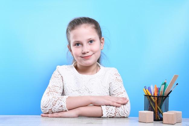 Voltar para a escola. criança industrioso bonito feliz está sentado em uma mesa dentro de casa. garoto está aprendendo em sala de aula.