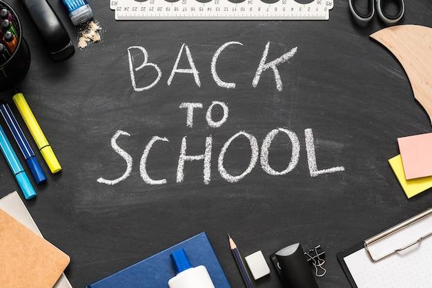 Voltar para a escola letras de giz branco sobre quadro negro.