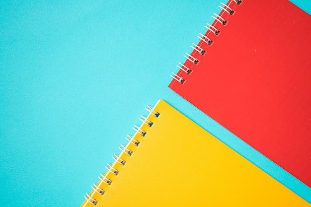 Voltar para a escola mock up. composição plana leiga com caderno vermelho e amarelo. conceito isométrico sobre fundo azul. arte pop. material escolar. a sobrecarga. branding mock up papelaria. educação
