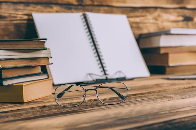Voltar para a escola mockup. caderno com livros e óculos no espaço de madeira.