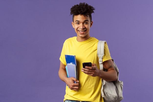 Voltar para a escola, o conceito de universidade. retrato de jovem homem sorridente bonito, estudante pedindo número de telefone do colega, anotando no celular, usar mochila, segurar cadernos e material de estudo