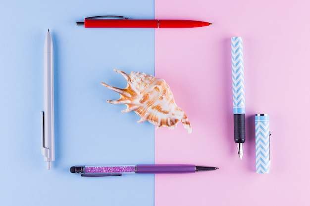 Voltar para a escola pop art. artigos de papelaria da escola e concha no azul rosa. postura plana. copyspace