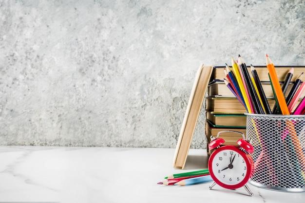Voltar para a mesa da escola com livros antigos, despertador, lápis