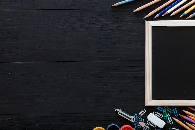 Voltar para o fundo da escola com material de papelaria para ensino fundamental moderno, lápis de cor, tintas e moldura na mesa do aluno de madeira preta escura, cópia livre espaço para texto, vista superior de cima