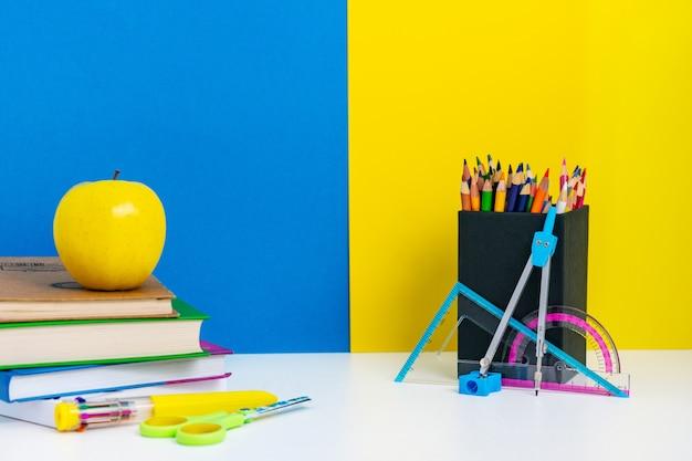 Voltar para o layout da escola com livros, lápis e maçã na mesa branca, parede azul e amarela, conceito de escola