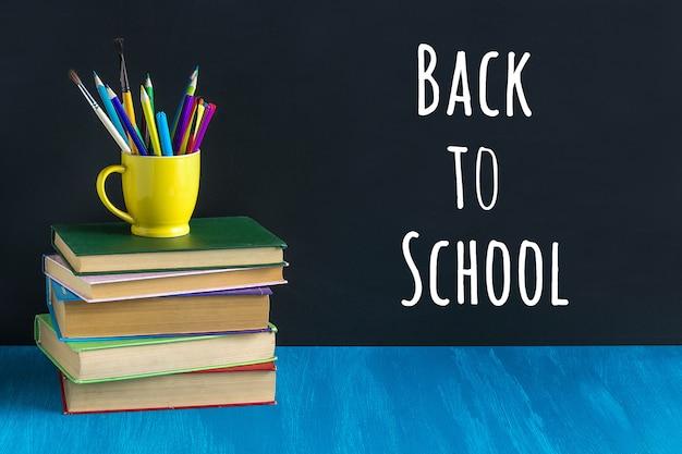 Voltar para o texto da escola na lousa preta e artigos de papelaria em uma caneca amarela na pilha de livros na mesa azul.