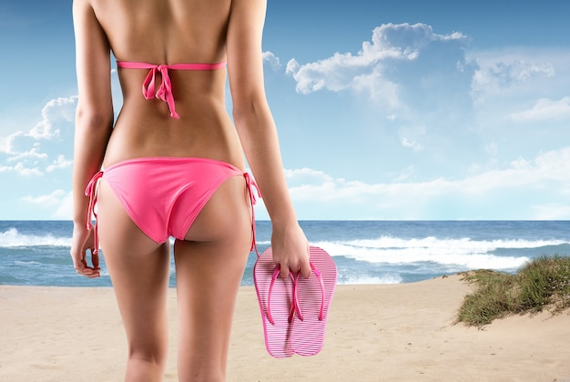Voltar retrato de mulher bonita com chinelos em uma praia