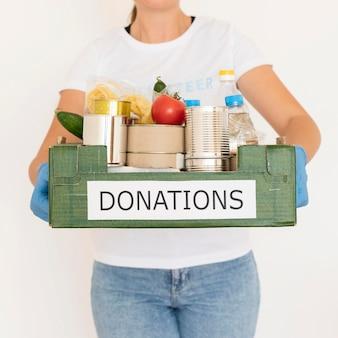 Voluntária com luvas segurando uma caixa de doação de alimentos