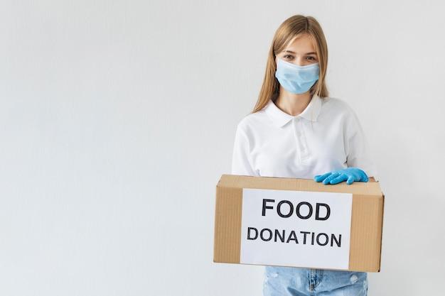 Voluntária com máscara médica e luvas segurando uma caixa de doações