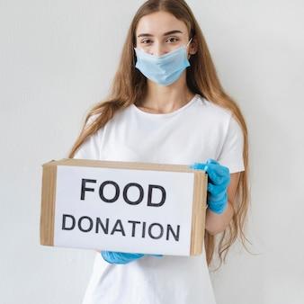 Voluntária com máscara médica segurando uma caixa de doação