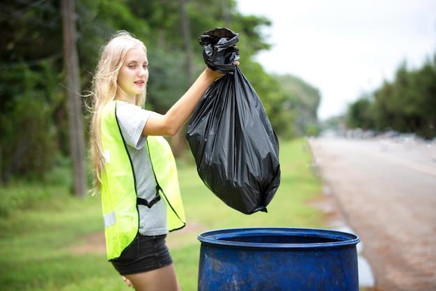 Voluntária segurando um saco de lixo de plástico, pegando o lixo e colocando-o em um saco de lixo preto.