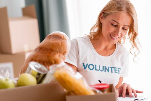 Voluntária sorridente ajudando com doações de alimentos