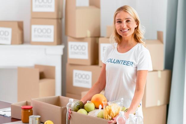 Voluntária sorridente segurando uma caixa com comida para doação