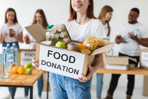 Voluntária sorridente segurando uma caixa de doações com comida