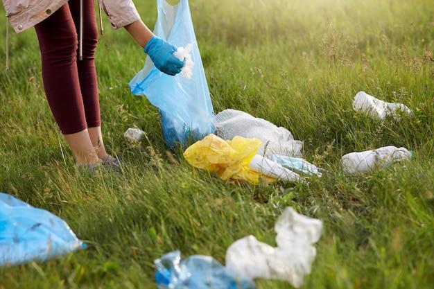 Voluntária usando leggins e luvas, catando lixo no prado, usando um saco de lixo azul