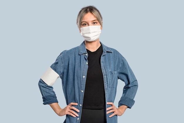 Voluntária usando uma máscara facial e um retrato de uma braçadeira