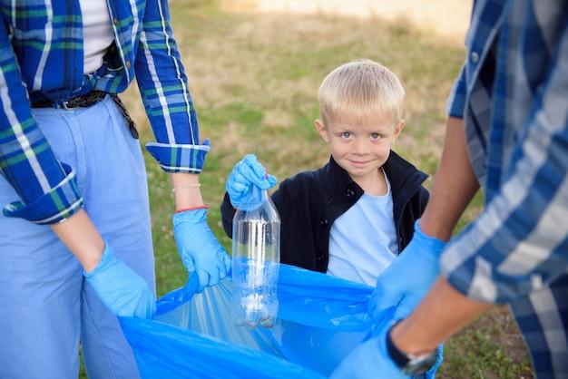 Voluntariado, caridade, pessoas e conceito de ecologia, voluntários usando saco de lixo durante a coleta de lixo