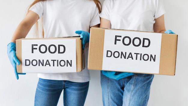 Voluntárias segurando caixas de doação de alimentos