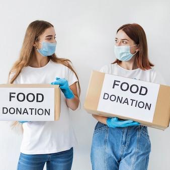 Voluntárias segurando caixas de doações
