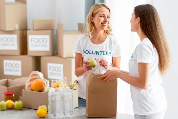 Voluntárias sorridentes colocando comida em sacolas e preparando-as para doação