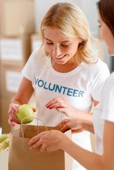 Voluntárias sorridentes colocando comida em um saco para doação