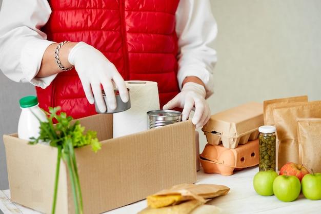 Voluntarie-se na máscara médica protetora e luvas colocando alimentos na caixa de doação.