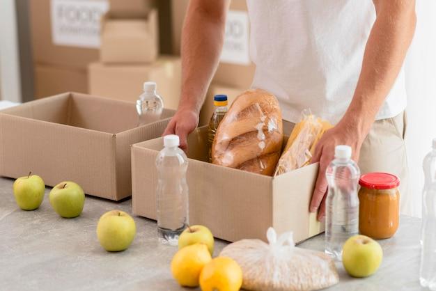 Voluntário ajudando com doações de alimentos em caixas