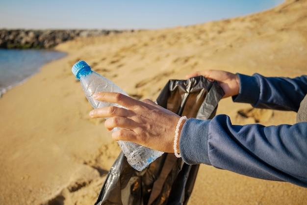Voluntário coleta lixo em um saco na praia