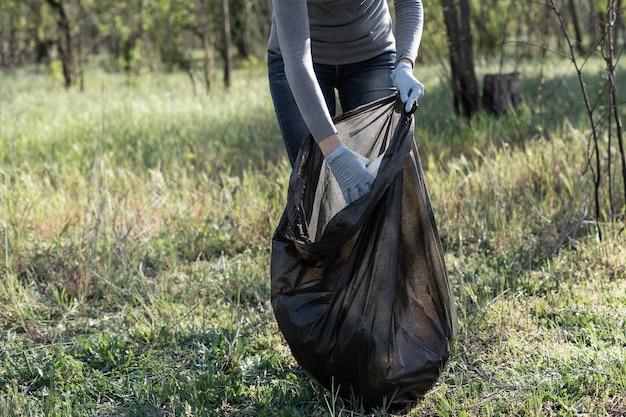Voluntário coleta lixo em um saco preto. mão feminina em uma luva de borracha. conceito de poluição ambiental