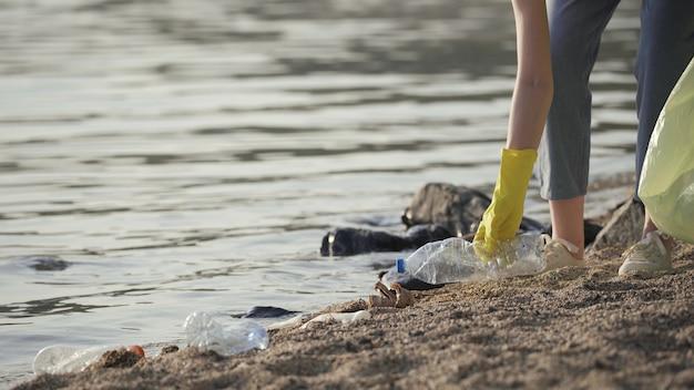 Voluntário coleta lixo plástico no parque. reciclar o conceito de ecologia de limpeza de garrafa de plástico fundo desfocado. luvas de voluntária de menina limpa coleta garrafas plásticas e copos em um saco de lixo.