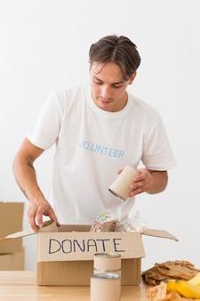 Voluntário colocando latas com comida em caixas