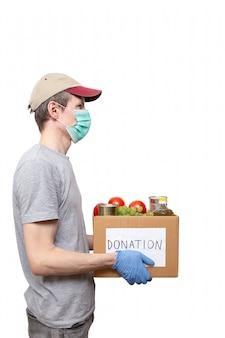 Voluntário com luvas de proteção azuis segurando comida de supermercado em uma caixa de papelão para doação