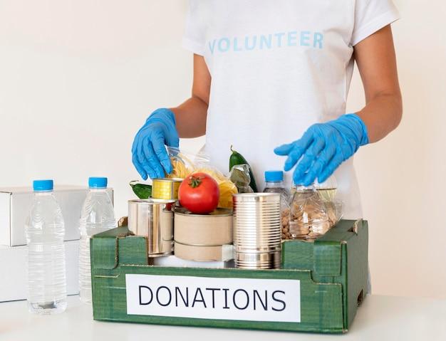 Voluntário com luvas lidando com caixa de doações de alimentos