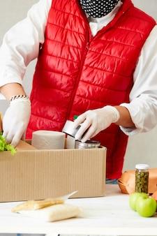 Voluntário com máscara médica protetora e luvas colocando alimentos na caixa de doação