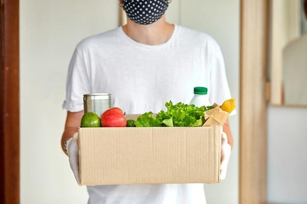 Voluntário com máscara protetora branca e luvas entrega caixa de doação em casa