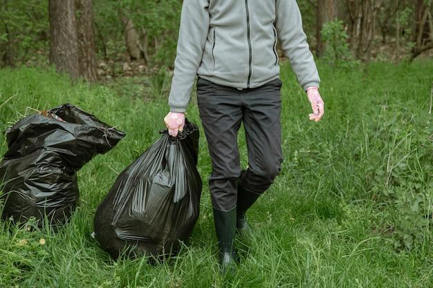 Voluntário com sacos de lixo em uma viagem à natureza, limpando o meio ambiente.