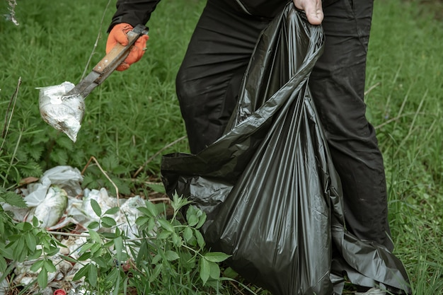 Voluntário com sacos de lixo em uma viagem à natureza, limpando o meio ambiente