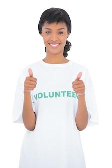 Voluntário de cabelo preto alegre dando polegares para cima