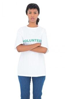 Voluntário de cabelo preto deprimido posando com braços cruzados