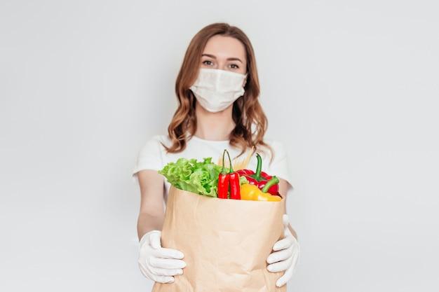 Voluntário de correio garota em uma máscara médica detém um saco de papel com produtos, legumes, ervas isoladas